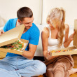 Romantic couple eating pizza at home - Stock Photo