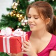 Happy woman with gift box and christmas tree — Stock Photo #13181201