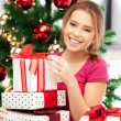 Happy woman with gift box and christmas tree — Stock Photo #13181208