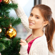 Woman decorating christmas tree - Stock Photo