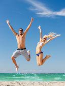 幸せなカップル、ビーチ上にジャンプ — ストック写真