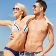 Happy couple in sunglasses on the beach — Foto de stock #13219754