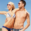 Happy couple in sunglasses on the beach — Stock fotografie