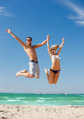 Happy couple jumping on the beach — ストック写真