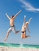 Happy couple jumping on the beach — Stok fotoğraf
