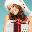 Cheerful santa helper girl with gift box — Stock Photo