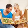 Romantic couple eating pizza at home — Stock fotografie