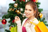 Happy woman with shopping bags and christmas tree — Stockfoto
