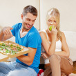 Couple eating different food - Stock Photo