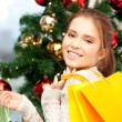 Happy woman with shopping bags and christmas tree - Stock Photo