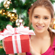 Happy woman with gift box and christmas tree — Stock fotografie
