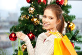 Happy woman with shopping bags and christmas tree — Stock Photo