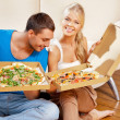 Romantic couple eating pizza at home — ストック写真