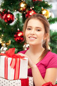 Happy woman with gift box and christmas tree — Stock Photo