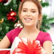 Happy woman with gift box and christmas tree - Stok fotoğraf