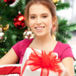 Happy woman with gift box and christmas tree - Lizenzfreies Foto
