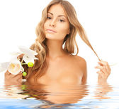 Beautiful woman with orchid flower in water — Stock Photo