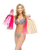 Mujer seductora en bikini con bolsas de compras — Foto de Stock