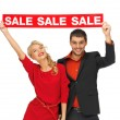 Man and woman with sale sign — Stock Photo