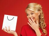 Hermosa mujer en vestido rojo con bolsa de compras — Foto de Stock
