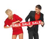 男人和女人与出售标志 — 图库照片