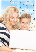 Happy mother and child with laptop computer — Stock Photo