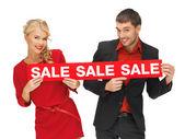 Man och kvinna med försäljning tecken — Stockfoto