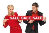 Hombre y mujer con cartel de venta — Foto de Stock