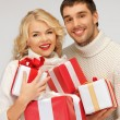 Family couple in a sweaters with gift boxes — Stock Photo #14421195