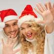 Family couple in sweaters and santa's hats — Stock Photo #14421401