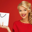 Lovely woman in red dress with shopping bag — Stock Photo #14495617