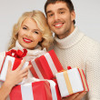 Family couple in a sweaters with gift boxes — Stock Photo #14496055