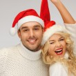Foto Stock: Family couple in sweaters and santa's hats