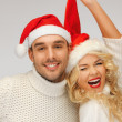 Stock Photo: Family couple in sweaters and santa's hats