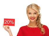 Lovely woman in red dress with discount card — Stock Photo