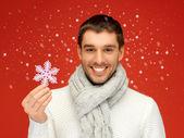 Man in warm sweater and scarf with snowflake — Stock Photo