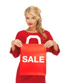 Beautiful woman in red dress with shopping bag — Stock Photo