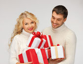 Family couple in a sweaters with gift boxes — Stock Photo