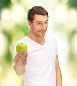 Man in white shirt with green apple — Stock Photo