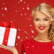 Lovely woman in red dress with present — Stock Photo