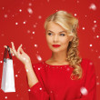 Lovely woman in red dress with shopping bag - Stock Photo