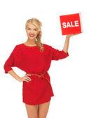 Mooie vrouw in rode jurk met verkoop teken — Stockfoto