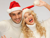 Family couple in sweaters and santa's hats — Stock Photo