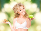 Woman choosing between burger and apple — Stock Photo