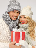 Romantic couple in a sweaters with gift box — Stock Photo