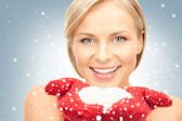 Beautiful woman in red mittens with snow — Stock Photo