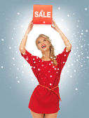 Härlig kvinna i röd klänning med försäljning tecken — Stockfoto