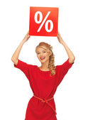 Mooie vrouw in rode jurk met procentteken — Stockfoto