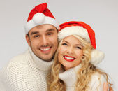 Family couple in sweaters and santa's hats — Foto de Stock