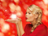 Woman blowing something on the palms of her hands — Stock Photo